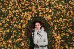 Fall portrait of a girl lying on a lawn in a forest park. Long hair on yellow foliage. royalty free stock images