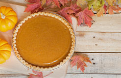 Fall Pumpkin Pie. Whole pumpkin pie with colorful fall leaves royalty free stock photos