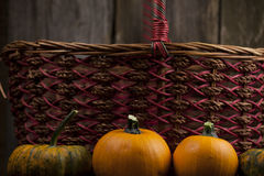 Fall pumpkins with woven basket. Fall pumpkins with red  woven basket and rustic background Stock Image