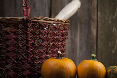 Fall pumpkins with woven basket. Fall pumpkins with  woven basket and rustic background Royalty Free Stock Photography