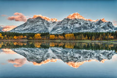 Fall reflection. Golden mountain peaks and autumn colours reflecting in Wedge Pond in Kananaskis Alberta Stock Image