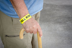 Fall Risk Bracelet And Wooden Cane. Fall risk bracelet around an elderly man's wrist while walking with a wooden cane stock images