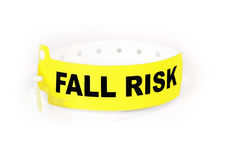 Fall Risk Patient ID Band. A yellow and black band utilized by health care facilities to identify patients that may easily fall due to various medical factors stock images