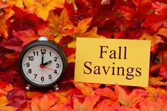 Fall Savings message. Some fall leaves and retro alarm clock and yellow card with text Fall Savings stock image