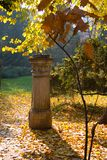 Fall scene. Fall in the park and old monument Royalty Free Stock Photos