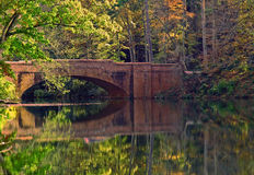 Fall scene. A nice fall scene of a stone arched bridge reflecting on the water of a still pond Royalty Free Stock Photo