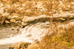 Fall scene of a man made waterfall. In a small steam with a rocky shoreline Royalty Free Stock Image