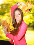 Fall season. girl holding autumnal leaves in park Stock Photo