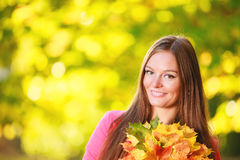 Fall season. Portrait girl woman with bunch of autumnal leaves Stock Image