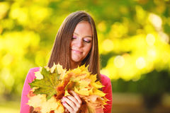 Fall season. Portrait girl woman with bunch of autumnal leaves Stock Photos