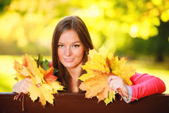 Fall season. Portrait girl woman holding autumnal leaves in park royalty free stock image
