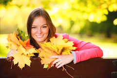 Fall season. Portrait girl woman holding autumnal leaves in park Stock Photos