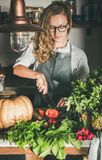 Young woman cutting fresh herbs and vegetables for cooking stock photography