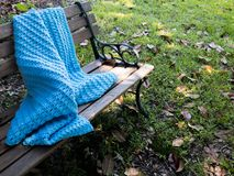 Crocheted Blanket on park bench in Autumn Stock Images