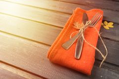 Fall serving perspective table with fork, knife and napkin over. Toned fall serving perspective table with fork, knife and orange napkin over wooden background stock image