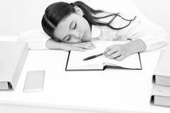 Fall sovande på kurs Flickabarnet faller sovande medan bakgrund för läseboktabellvit Skolflicka som tröttas av att studera arkivfoton