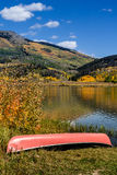 Fall in Steamboat Springs Colorado. Bright red canoe sitting on shore of mountain lake on fall afternoon with brightly colored changing Aspen trees on slopes Stock Photography