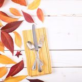 Fall Table Place Setting Invite Card with Brown and Gold Leaves, Silverware, and Napkin Flat Lay on White Shiplap boards backgrou