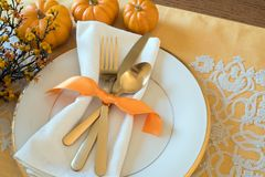 Fall Thanksgiving or Halloween Table Place Setting and pumpkins in Gold tones. Horizontal with natural lighting from above, lookin