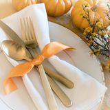 Fall Thanksgiving or Halloween Table Place Setting and pumpkins in Gold tones. Square with warm natural lighting from above lookin stock images