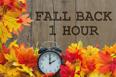 Fall Time Change. Autumn Leaves and Alarm Clock with grunge wood with text Fall Back 1 Hour Stock Photography