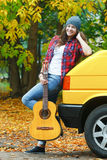 Fall time full length portrait of cheerful guitarist girl travelling by yellow van Royalty Free Stock Images