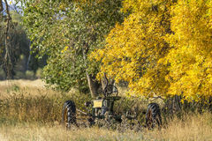 Fall tractor. An old vintage john deere tractor at rest in a farmers field with fall color stock image