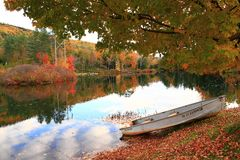 Fall in Vermont. Littlle boat at a lake in Vermont. Beautiful fall reflections in the water. Autumn folliage. Clouds reflection in the water stock photography