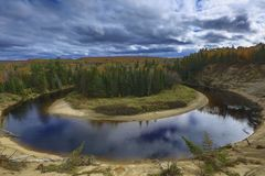 Fall Winding River seen from top of moutain. At Algonquin area. the river is reflecting the blue sky, it is a cloudy day, leaves are becoming yellow. fall is royalty free stock photo