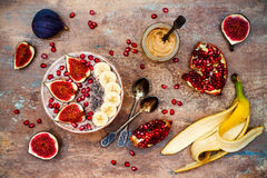 Fall and winter breakfast set. Acai superfoods smoothies bowl with chia seeds, pomegranate, banana, fresh figs, hazelnut butter. stock photos
