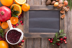 Fall and winter ingredients chalkboard frame. Fall and winter ingredients background with chalkboard, oranges, cranberry, nuts and spices Royalty Free Stock Images