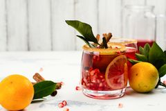 Fall and winter sangria. Red fall or winter cocktail drink with pomegranate, lemon, tangerines and cinnamon on white stone table. Selective focus Royalty Free Stock Photography