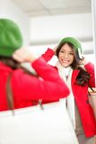 Fall / Winter shopping woman. Trying on knit hat looking in mirror smiling happy holding shopping bags inside in clothing store. Multiracial shopper woman Royalty Free Stock Photography
