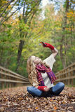 Fall woman. A happy young woman sitting on a path in fall holding up colorful leaves. Autumn royalty free stock photography
