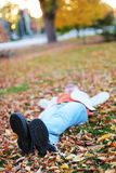 Fall woman. Young woman lying down in the leaves Stock Photography