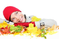 Fall woman happy with colorful Autumn leaves. Isolated on white background in studio. Thinking girl portrait close up resting face on leaves looking up. Mixed Royalty Free Stock Photo