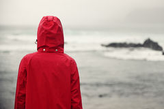 Fall woman in rain looking at ocean Stock Photos