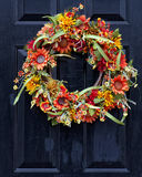 Fall Wreath. Autumn wreath on black door made from fall flowers Stock Photos