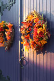 Fall wreaths on door. A view of wreaths of fall leaves and flowers hung on a wooden door Royalty Free Stock Photo