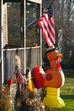 Fall: yard with Thanksgiving decorations and flag. Yard with inflatable turkey, scarecrows and US flag decorations Royalty Free Stock Image