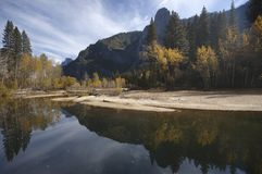 Fall in Yosemite - river Merced. The fall colors and gray granite cliffs of Yosemite reflected in smooth water of Merced river Stock Image