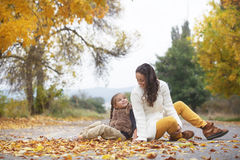 Fall. Young mother with her little daughter walking in fall park on yellow fallen leaves one autumn day stock photo