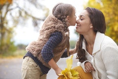 Fall. Young mother with her little daughter walking in fall park on yellow fallen leaves one autumn day royalty free stock photos