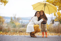 Fall. Young mother with her little daughter walking in fall park on yellow fallen leaves one autumn day royalty free stock photo