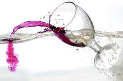 Falla ett exponeringsglas av rött vin in i vatten Royaltyfria Foton