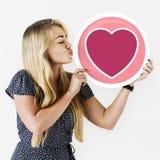 Fallande förälskad emoticon för lyckligt kvinnainnehav arkivbilder