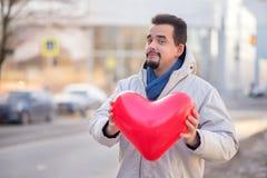 Fallande förälskad metafor: stående av en le skäggig vuxen man som rymmer med två händer och bort ger stor röd hjärta formad luft royaltyfri foto