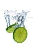 fallande limefrukt skivar vatten Fotografering för Bildbyråer