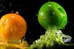 fallande nya frukter plaskar vatten arkivfoto
