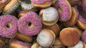 Fallande olika donuts på en rosa bakgrund lager videofilmer